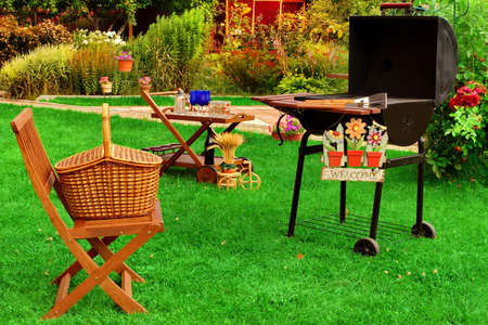 Photo pour Garden Wooden Furniture, Picnic Hamper Basket, BBQ Grill, Sign Welcome, Wine Glasses On The Table, Plants, Trees and House In The Background. Backyard  BBQ Grill Party Or Picnic Concept - image libre de droit