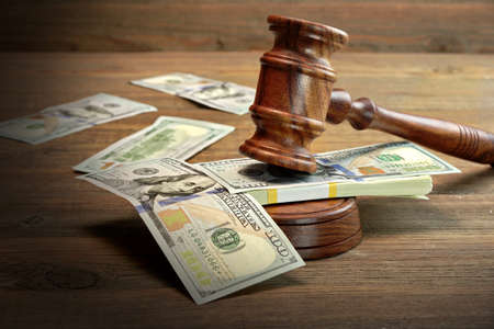Photo pour Concept For Corruption, Bankruptcy Court, Bail, Crime, Bribing, Fraud, Auction Bidding. Judges or Auctioneer Gavel, Soundboard And Bundle Of Dollar Cash On The Rough Wooden Textured Table Background. - image libre de droit