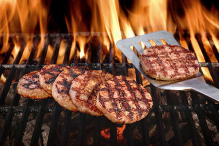 Photo pour Beef Burgers And Spatula On The Hot Flaming BBQ Charcoal Grill, Close-up, Top View - image libre de droit