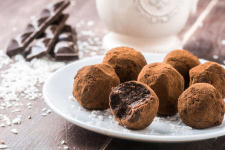 Photo for Homemade healthy vegan chocolate truffles with dates, coconut flakes and rolled oats served on white plate - Royalty Free Image