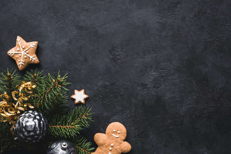 Photo for Christmas background. Gingerbread cookies, fir tree, christmas toys and holiday decorations frame on blackboard or stone backdrop. Top view with copy space for text - Royalty Free Image