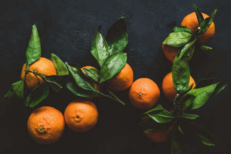 Photo for Tangerines or clementines with green leaf. Still life on dark background. Top view, toned image - Royalty Free Image