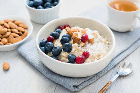 Photo for Oatmeal porridge bowl with blueberries, cranberries and almonds and cup of green tea. Concept of healthy lifestyle, healthy eating, fitness menu and dieting - Royalty Free Image