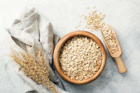 Foto de Rolled oats in wooden bowl and ears of wheat on grey background. Table top view. Healthy eating, healthy lifestyle, gluten free diet concept - Imagen libre de derechos