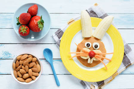 Photo pour Healthy Easter Breakfast For Kids. Easter Bunny Shaped Pancake With Fruits. Top View - image libre de droit