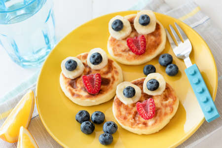 Photo pour Fun food for kids. Pancakes with funny animal faces on colorful yellow plate. Kids meal. Selective focus - image libre de droit