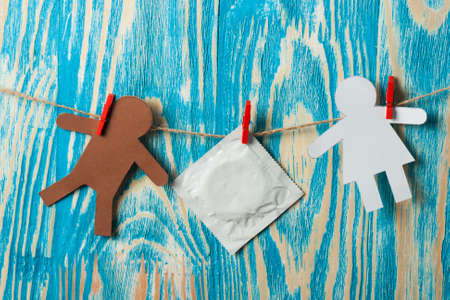 Foto de Thumb and condom over  on wood desk. World AIDS Day - Imagen libre de derechos