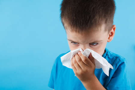 Photo pour Child blow the nose. Asian boy using tissue to wipe snot from his nose and free form copy space. Illness child with allergy symptom. Isolated on blue background. Studio shot. - image libre de droit