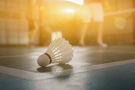 Foto de A set of badminton concept.Badminton ball (shuttlecock) and racket on court floor,Paddle ,the shuttlecock and badminton courts with players competing in modern gym,selective focus,vintage color - Imagen libre de derechos