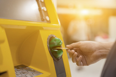 Photo pour Hand inserting ATM card into bank machine to withdraw money,People stand in a queue to use the ATMs of a bank. Person receiving money from the ATM.vintage color - image libre de droit