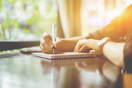 Foto de female hands with pen writing on notebook on wooden table ,young girl writing into her diary, in the park,Woman writing recipient address on mailing envelope,female hands sending letter,vintage color - Imagen libre de derechos