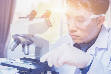 Foto de Science and technology concept ,Serious clinician student studying chemical element in laboratory,medical or scientific researcher or doctor using looking at solution in a laboratory,vintage color - Imagen libre de derechos