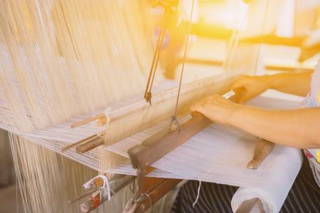 Foto de weave silk cotton on the manual wood loom inlaos handicraft ,thailand,selective focus,vintage color - Imagen libre de derechos