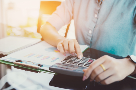Foto de Businesswomen bookkeeper or financial inspector hands making report, calculating or checking balance on calculator. Home finances, investment, economy, saving money or insurance concept,vintage color - Imagen libre de derechos