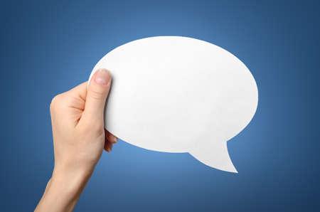 Photo pour Hand holding an empty speech bubble on blue  - image libre de droit