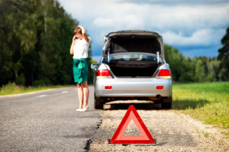 Foto de Close up on triangle warning sign with woman calling for assistance after breaking down with her car on background - Imagen libre de derechos