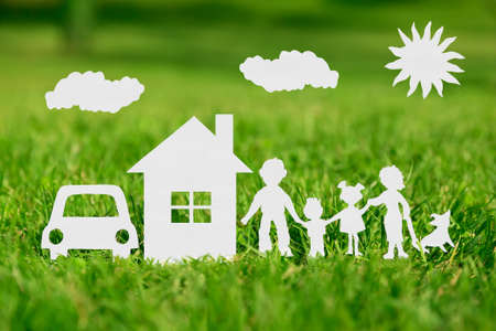 Foto de Paper cut of family with house and car on green grass - Imagen libre de derechos