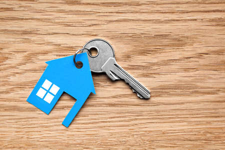 Foto de Silver key with blue house figure on wooden background - Imagen libre de derechos
