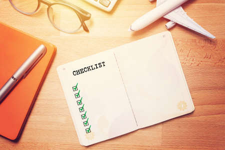 Photo pour travel checklist concept. notebook with blank checklist on wooden background with glasses and plane model - image libre de droit