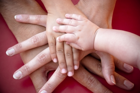 Photo for Four hands of the family,  a baby, a daughter,  a mother and a father. Concept of unity, support, protection and happiness. - Royalty Free Image