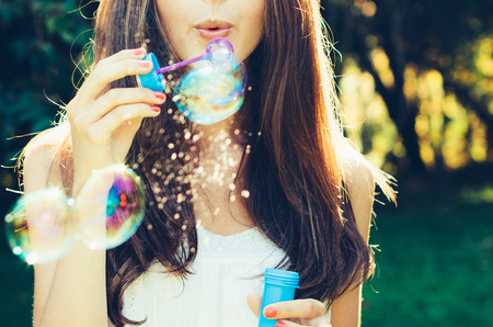 Photo for Girl blowing bubbles outdoor. Focus on lips. - Royalty Free Image