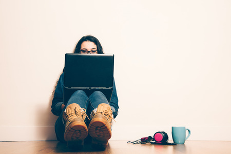 Foto de Girl sitting on the floor with a laptop looking at screen concentrated. Filter effect added. - Imagen libre de derechos