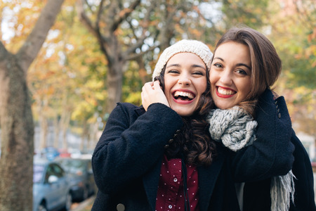 Photo for Laughing best friends hugging outdoors in autumn - Royalty Free Image
