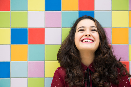 Foto de Happy girl laughing against a colorful tiles background. Concept of joy - Imagen libre de derechos