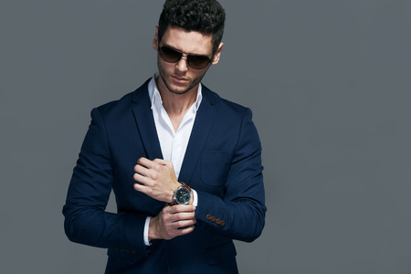 Photo pour Elegant young handsome man wearing glasses and wathers. - image libre de droit
