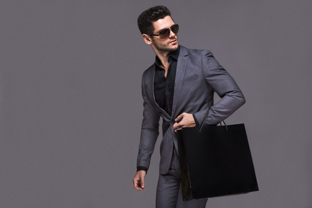 Photo pour Handsome man in suit with shopping bag - image libre de droit