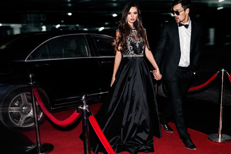 Photo for Sexy couple in the car. Hollywood star. Fashionable pair of elegant people at night city street. - Royalty Free Image