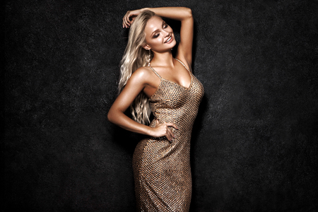 Foto de Beautiful sexy blonde woman on black background, party. - Imagen libre de derechos