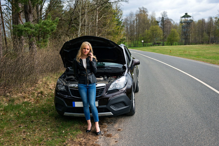 Foto de young attractive desperate and confused woman stranded on roadside with broken car engine failure crash accident calling on mobile phone for mechanic assistance in insurance company concept - Imagen libre de derechos