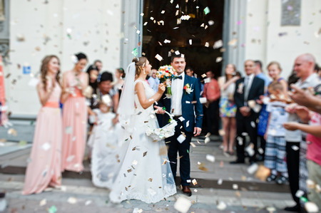 Photo pour wedding couple come out from church under petals of roses. blur effect - image libre de droit