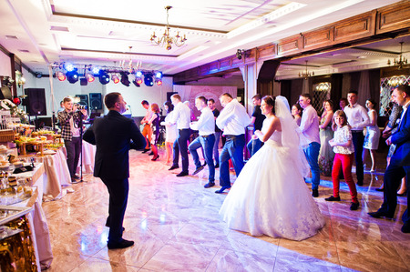 Photo pour Petryky, Ukraine - May 14, 2016: Dance wedding party with guests and leading toastmaster - image libre de droit