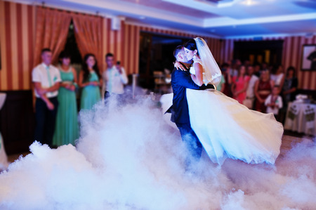 Photo pour Beautiful couple dancing in the restaurant with different lights and smoke on their wedding day. - image libre de droit