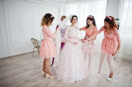 Photo pour Helpful bridesmaids and mother helping bride to tie the dress up in big light room.a - image libre de droit