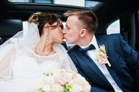 Photo pour Beautiful wedding couple sitting in the car, looking into each other's eyes and kissing. - image libre de droit
