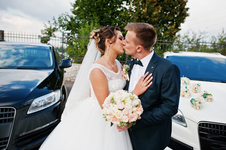 Photo pour Gorgeous wedding couple enjoying each other's company next to wedding suvs. - image libre de droit