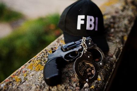 Foto de FBI cap with revolver and handcuff. - Imagen libre de derechos