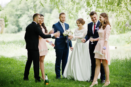 Photo pour Wedding couple, bridesmaids and groomsmen drinking champagne on a festive wedding day in the park. - image libre de droit