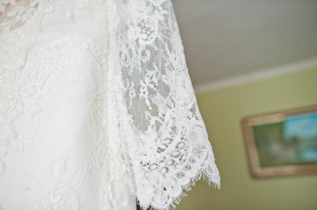 Photo for Bride's wedding dress hanging on the hanger in the room. - Royalty Free Image