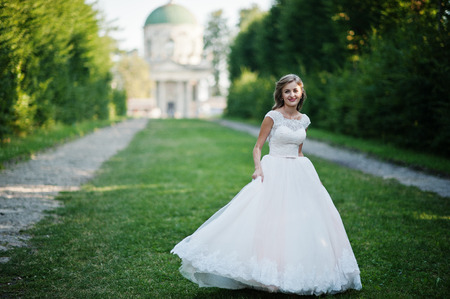 Photo pour Lonely attractive bride walking on the green alley which leads to a church. - image libre de droit