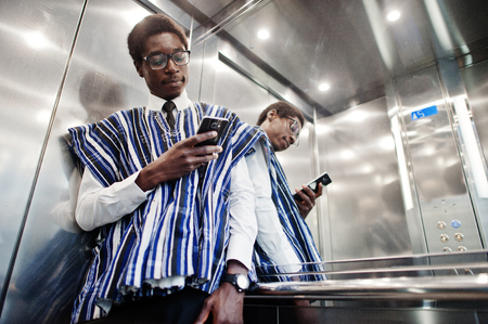 Foto de African man in traditional clothes and glasses with mobile phone at elavator or modern lift. - Imagen libre de derechos