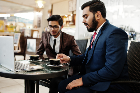 Foto de Two indian business man in suits sitting at office on cafe, looking at laptop and drinking coffee. - Imagen libre de derechos