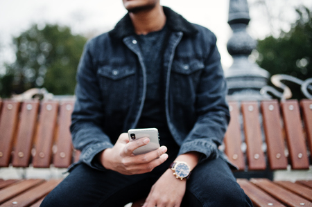 Photo for Handsome and fashionable indian man in black jeans jacket posed outdoor, sitting on bench with mobile phone at hand. - Royalty Free Image