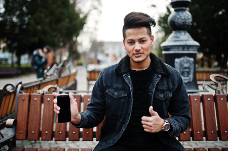Photo for Handsome and fashionable indian man in black jeans jacket posed outdoor, sitting on bench with mobile phone at hand, showing thumb up. - Royalty Free Image