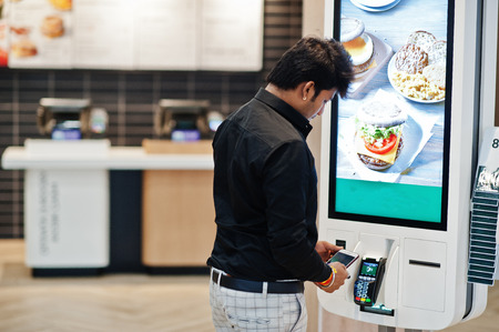 Photo pour Indian man customer at store place orders and pay by contactless credit card on mobile phone through self pay floor kiosk for fast food, payment terminal. Pay pass. - image libre de droit