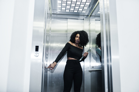 Photo for Fashionable young beautiful african american business woman with afro hairstyle wear in elegant black, stand at elevator with phone and laptop at hands. - Royalty Free Image