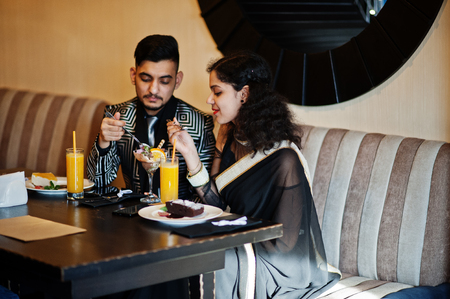 Foto de Lovely indian couple in love, wear at saree and elegant suit, sitting on restaurant and  eating ice cream together. - Imagen libre de derechos